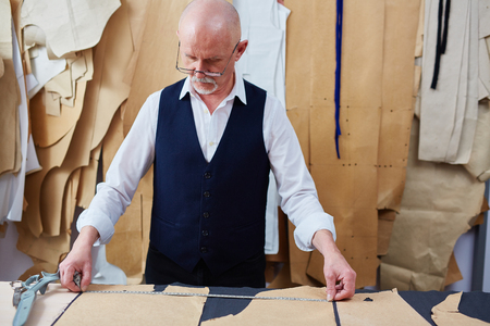 Experienced Tailor Working on Garments in Atelier Stock Photo