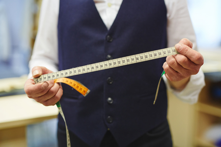 Closeup shot of unrecognizable tailor holding measuring tape in hands while working in traditional atelier studio