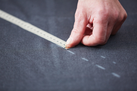 Closeup of skilled tailor working in atelier: hands marking and measuring fabric while making clothes Stok Fotoğraf