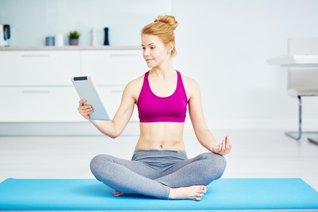Healthy Young Woman Practicing Yoga at Home Stock Photo