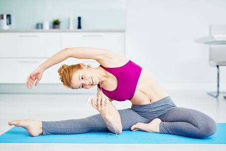 Glimlachende jonge vrouw die zich uitstrekt Oefeningen Stockfoto