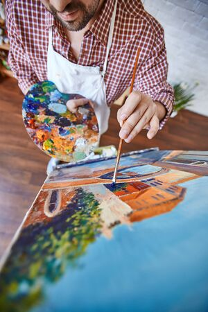 Artist Painting Beautiful Picture on Easel in Studio Stock Photo