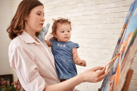 Young Woman Painting with Child in Art Studio Stock Photo
