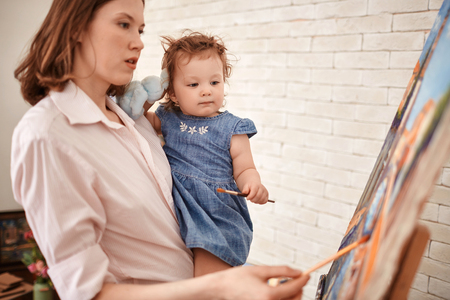 Young Mother Painting Picture with Little Girl