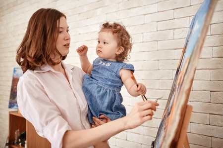Female Artist Painting In Art Studio with Little Child