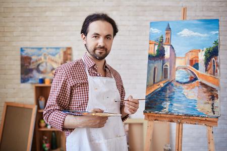 Kunstenaar poseren met olieverfschilderijen in kunststudio