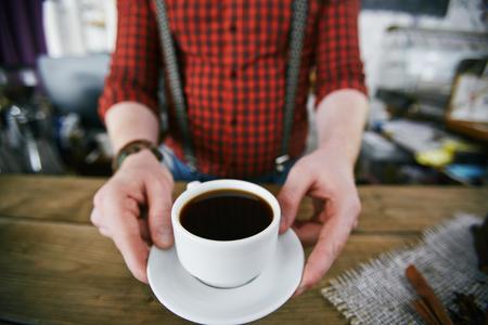 Trendy Barista entrega taza de café negro en la barra Foto de archivo - 79809376