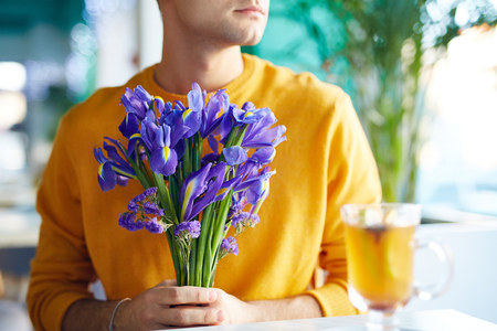 blind date: Young Man Holding Flowers Bouquet
