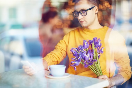 blind date: Young Man Using Smartphone Waiting for Date in Cafe