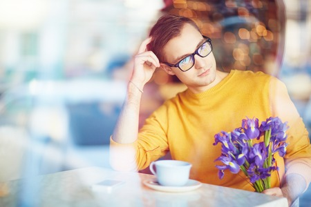 blind date: Daydreaming Man Waiting For Date in Cafe