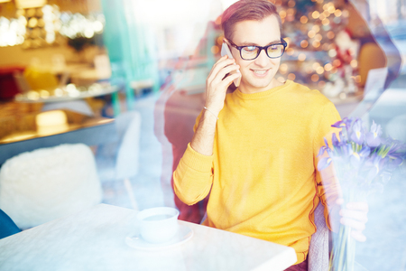 blind date: Smiling Young Man Waiting for Date in Cafe