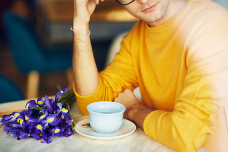 blind date: Portrait of unrecognizable young man waiting for romantic date in cafe with bouquet of flowers and cup of coffee