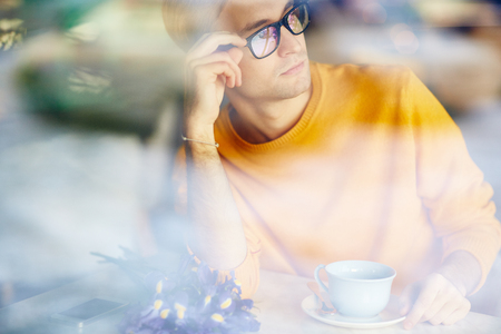 blind date: Pensive Young Man Looking Out of Cafe Window Stock Photo