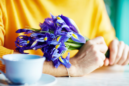 blind date: Closeup shot of young man holding bouquet of beautiful irises on date in cafe Stock Photo