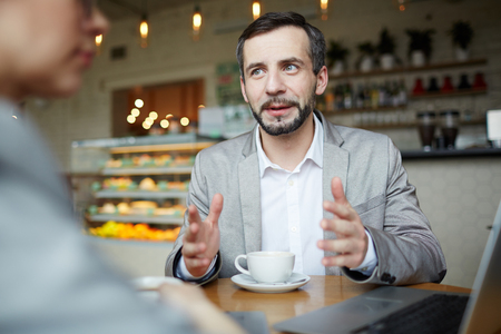 persuading: Mature Businessman Discussing Work at Meeting in Cafe Stock Photo