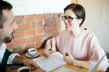 Smiling Businesswoman Explaining Contract Documents to Client in Stock Photo
