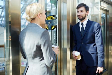 Twee mensen uit het bedrijfsleven chatten in lift Stockfoto