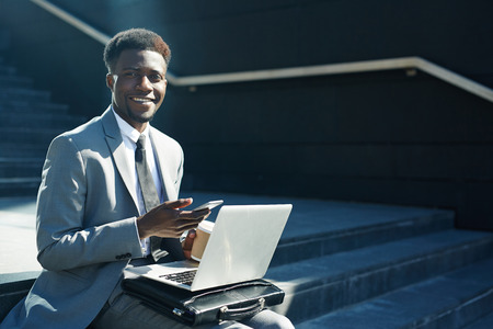 Successful specialist with modern gadgets looking at camera. Stock Photo