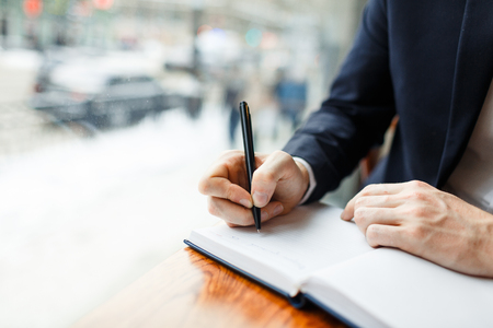 Zakenman met pen maken notities in notitieboekje