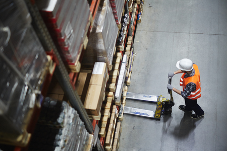 Above view of warehouse loader using forklift cart to pick up pallet with goods Stockfoto
