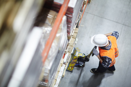 Above view of warehouse loader picking up heavy pellets  using forklift cart Stock Photo
