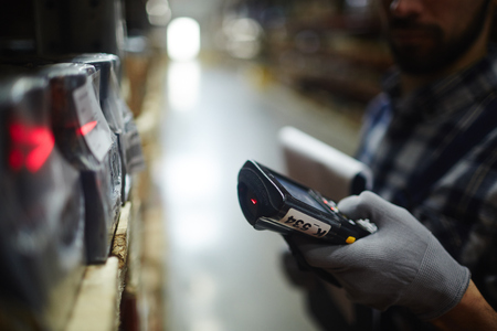 Side view closeup of bar code scanner in hand of unrecognizable warehouse worker doing inventory of stock Archivio Fotografico