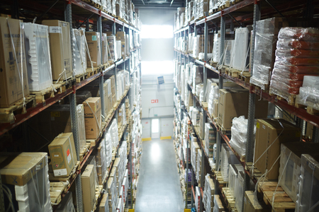 Rows of Shelves in Large Scale Warehouse Stock Photo
