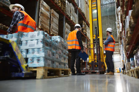 Warehouse Workers Loading Goods on Reach Fork Truck