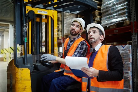 Two Warehouse Workers Riding Forklift Truck Stock Photo
