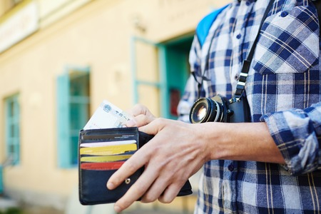 Closeup image of young tourist putting money in wallet, saving money  for vacation trips Stock fotó