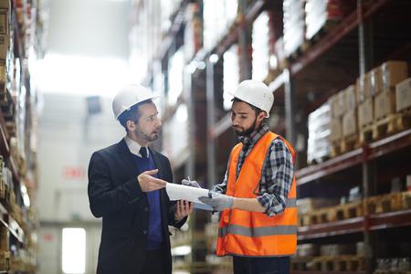 Supervisore del magazzino che parla con il costruttore di acquisto Archivio Fotografico - 82721561