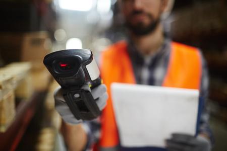 Primo piano di scanner di codici a barre in mano di operaio magazzino irriconoscibile facendo inventario delle scorte Archivio Fotografico - 82699514