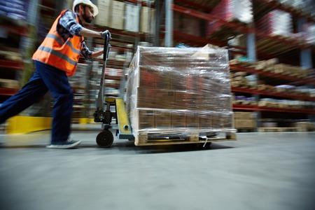 Worker Moving Retail Merchandise in Large warehouse Foto de archivo