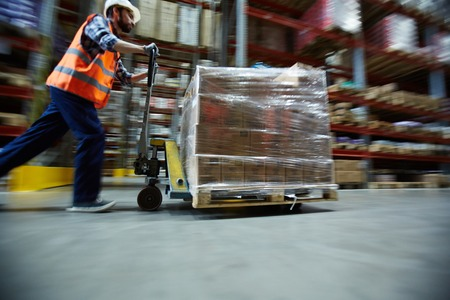 Worker Moving Retail Merchandise in Large warehouse Imagens