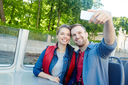 Young couple making selfie for their video-blog while traveling