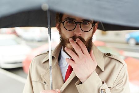 Smoking in rain Stock Photo