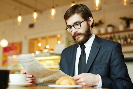 vacancy: Young specialist looking for new vacancies in newspaper Stock Photo