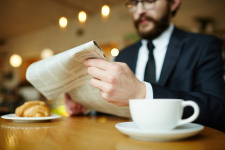 Newspaper in hands of jobless man having coffee in cafe Stock Photo - 83186960