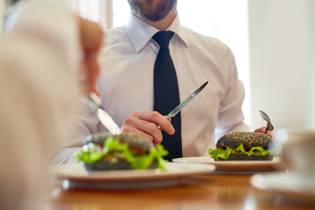 Businessman in shirt and tie holding knife and fork over hamburger on plate while talking to colleague by lunch