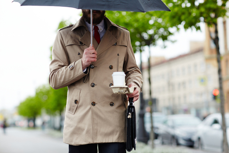 Businessman under umbrella carrying drink and briefcase Stock Photo