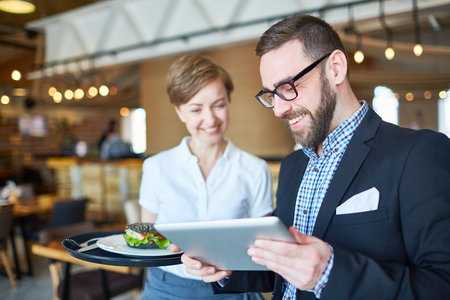 레스토랑에서 전자 메뉴로 비즈니스 점심을 선택하는 사업가