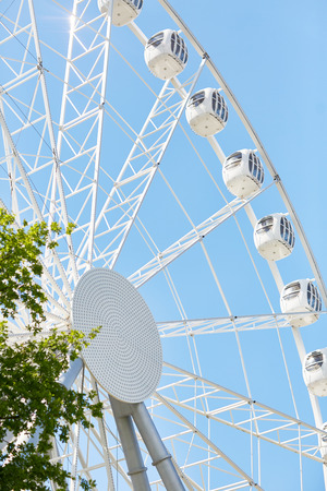 Angle view of tall modern Ferris wheel against blue sky in amusement park Stock Photo