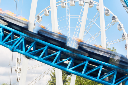 Background image of rolling rides in bustling modern amusement park Stock Photo
