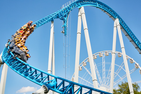 Tall roller coaster ride with trolley going down fast in blurred motion against clear blue sky