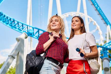 Portrait of two beautiful young women enjoying sunny day in amusement park standing against rides and Ferris wheel Stock Photo
