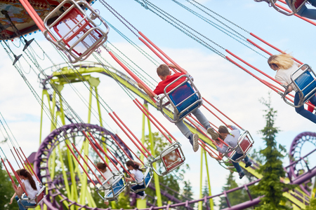Low angle shot of spinning seats of merry go round with children riding it Stock Photo