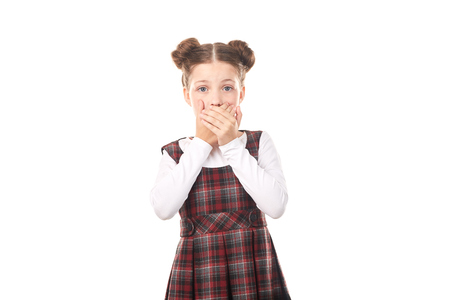 Portrait of cute girl in school uniform covering her mouth with hands against white background
