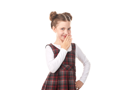 Portrait of naughty little girl in school uniform against white background