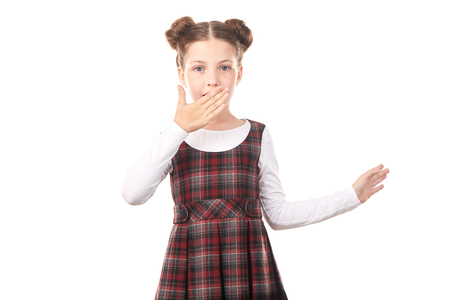 Portrait of cute girl in school uniform covering her mouth with hand against white background Stock Photo