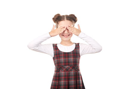 Portrait of cute girl in school uniform covering her eyes with hands against white background Banco de Imagens